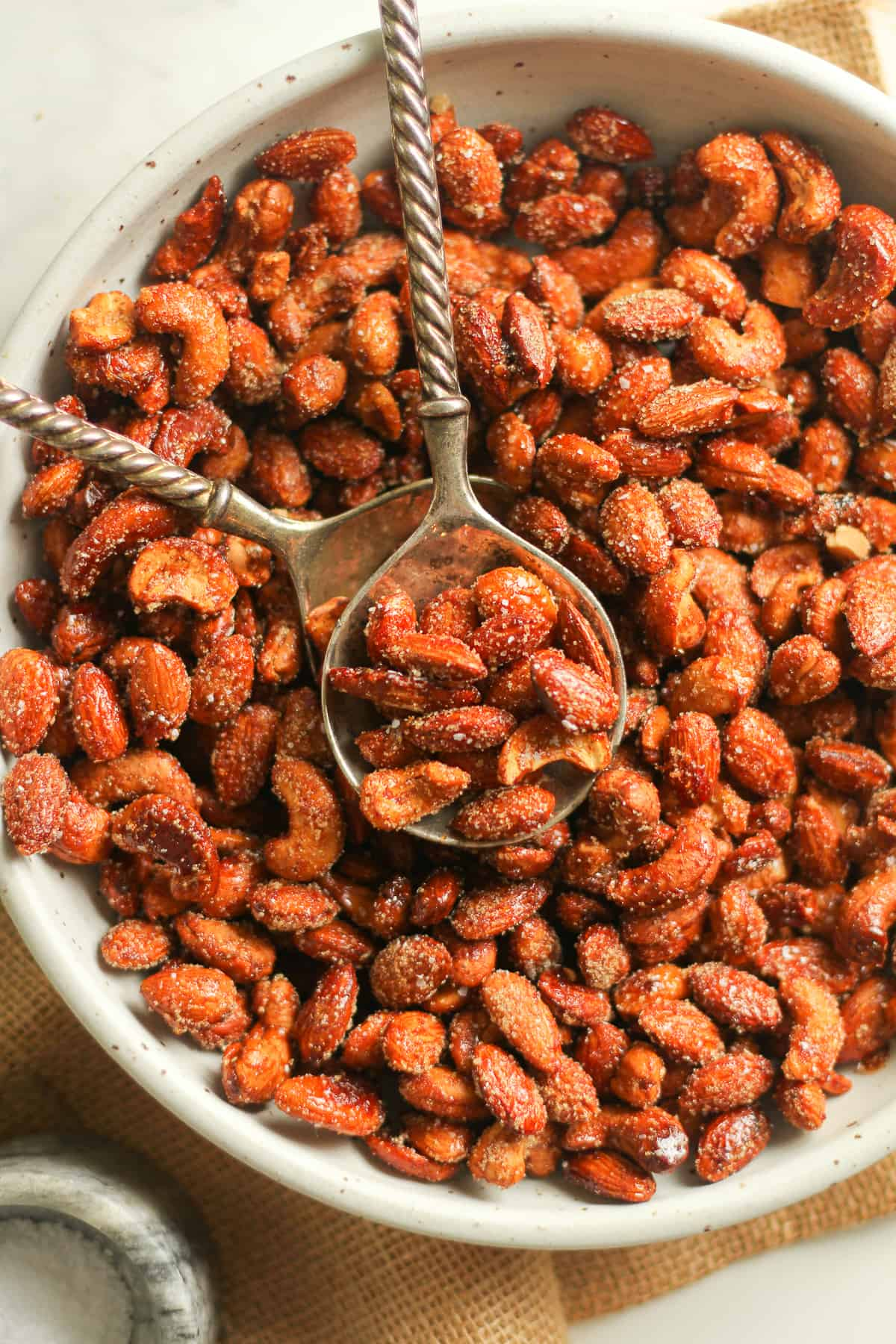 A bowl of the honey roasted nuts with serving spoons on top.