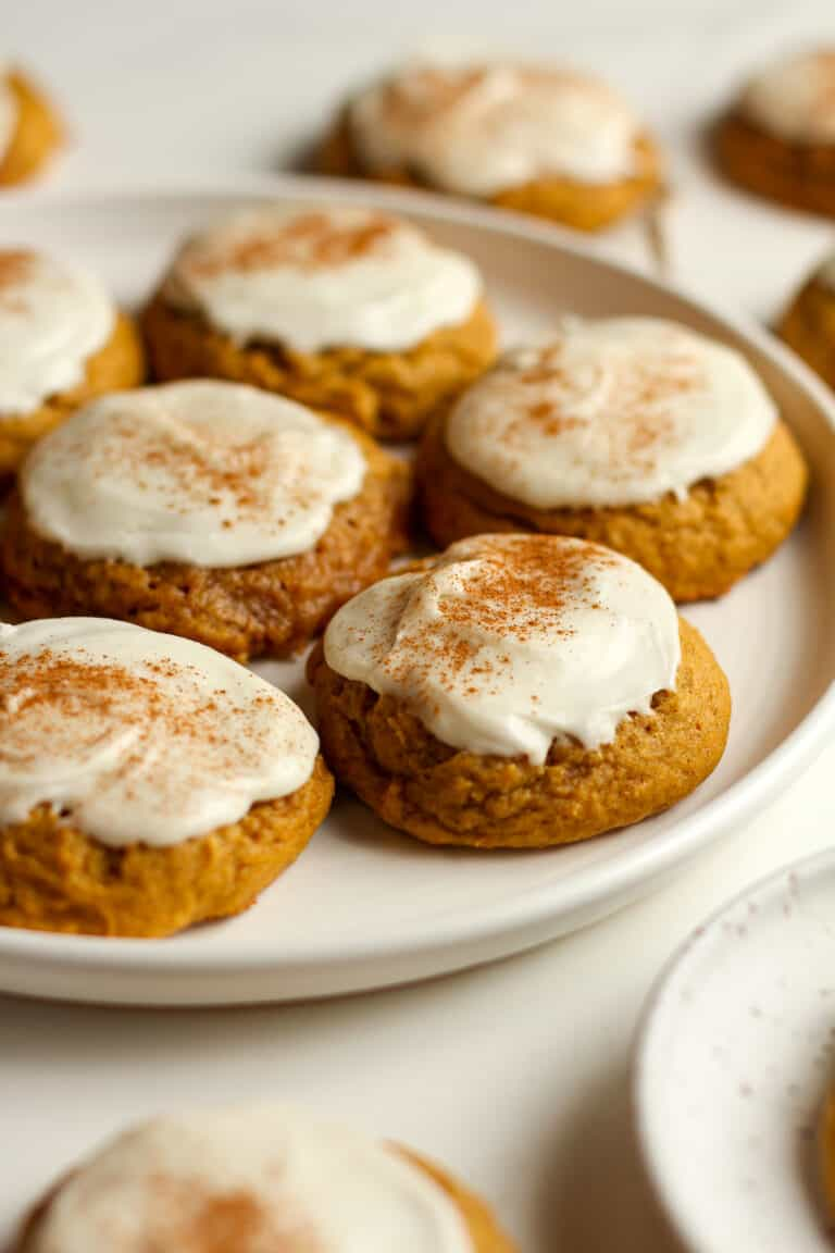 Side shot of a plate of iced pumpkin cookies.